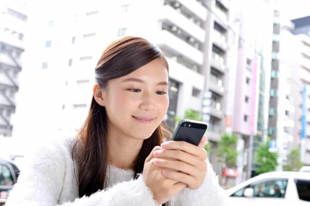 外でiPhoneを使う女性